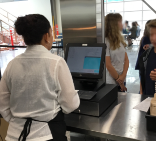 Register in use at a cafeteria, with students in line